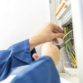 stock photo of fuse-box  - Electrician installing an electrical fuse box in a house working with pliers on the wiring circuits - JPG