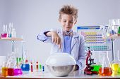 pic of naturalist  - Smiling boy conducting experiment in chemistry lab - JPG