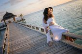 picture of fondling  - Happy loving couple in white clothes posing on a pier on Maldives - JPG