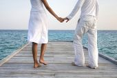 stock photo of caress  - Happy loving couple in white clothes posing on a pier on Maldives - JPG