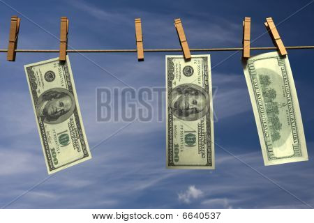 Hundred dollar bills hanging on a clothesline