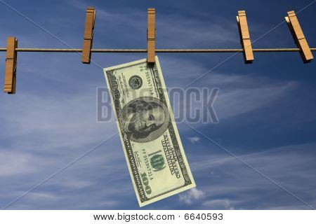 One hundred dollar bill hanging on a clothesline