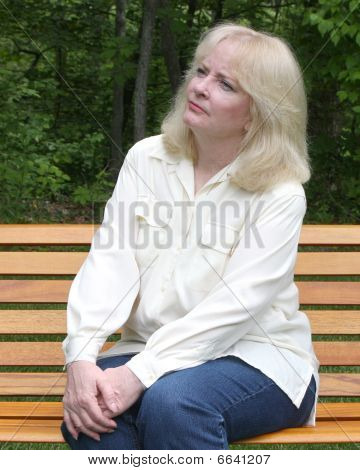 Older Woman Sitting On A Park Bench