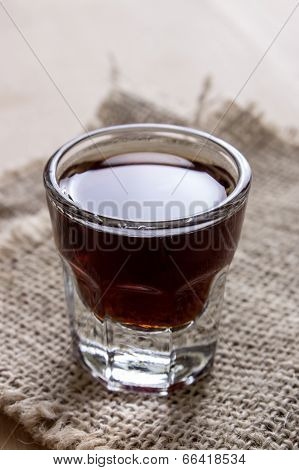Shot Of Alcohol On Wooden Table
