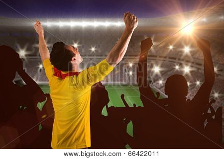 Cheering football fan in yellow jersey against large football stadium with lights