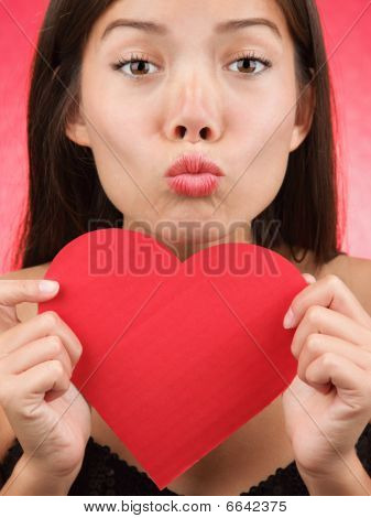 Cute Valentines Day Woman Kiss. Valentines day kiss? Woman blowing a kiss holding a Valentines Day heart sign. Beautiful mixed race chinese / caucasian
