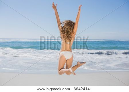 Fit woman in white bikini leaping on beach on a sunny day