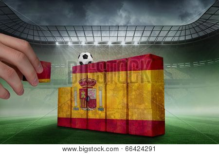 Hand building wall of spain flag in grunge effect