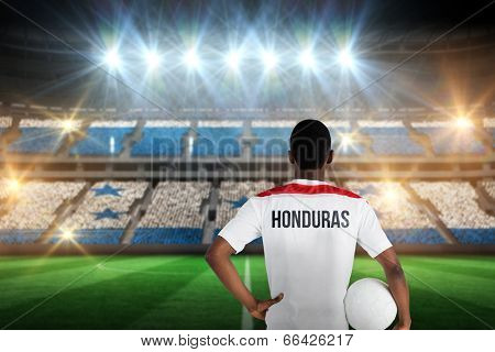 Honduras football player holding ball against stadium full of honduras football fans