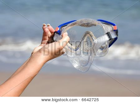 Womans Hand Holding Scuba Snorkelling Mask On Tropical Beach
