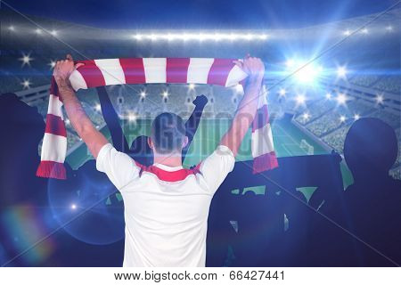 Football player holding striped scarf against large football stadium with lights