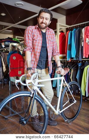 Portrait of a handsome man with bicycle looking at camera in sports shop