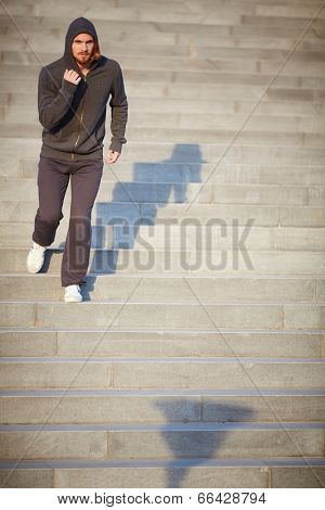 Portrait of young attractive sportsman running down steps