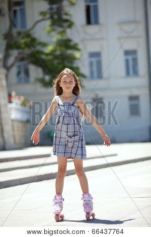 7 years old kid girl rollerskating in city street