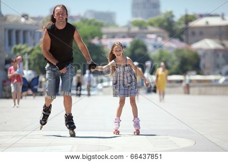 Father with his small daughter rollerskating in city street