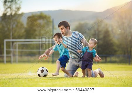 Father and sons playing football