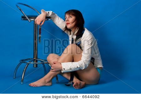 seminude young caucasian girl holding knife near high chair