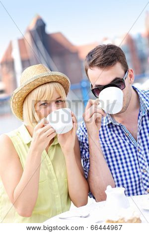 A picture of a young couple drinking coffee in an outside cafe in Gdansk marina