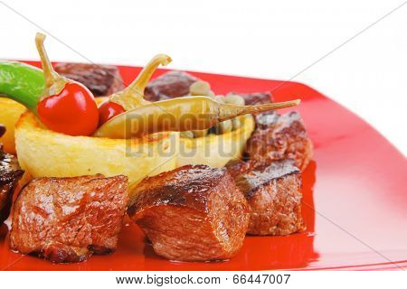 european food: grilled meat goulash on red plate with hot peppers, capers and olives oil, and bbq sauce
