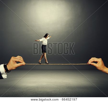 businesswoman balancing on the rope over dark background