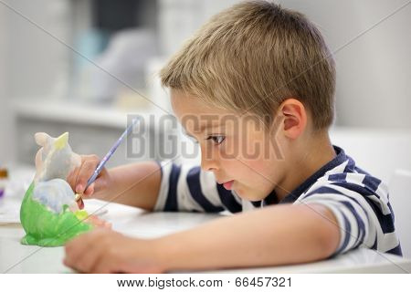 Child painting a ceramic pottery model at school concept for art and creative education
