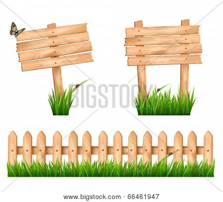 Two wooden signs and a fence with grass.