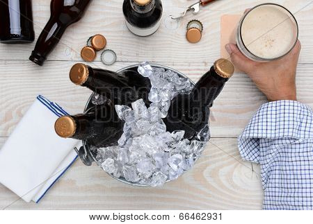 High angle shot of a man holding a glass of beer with a metal bucket with unopened bottles. The rustic wood table has empty bottles and caps and an bottle opener.