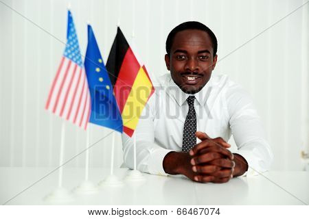 Cheerful businessman sitting at the table at his workplace