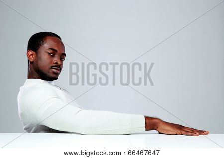 Thoughtful african man sitting at the table on gray background