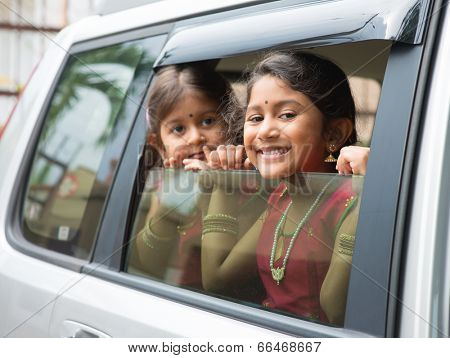 Asian Indian family going to a vacation. Happy children sitting inside car with window open looking out.