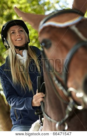 Closeup photo of attractive female rider on horseback. Photographed from below.