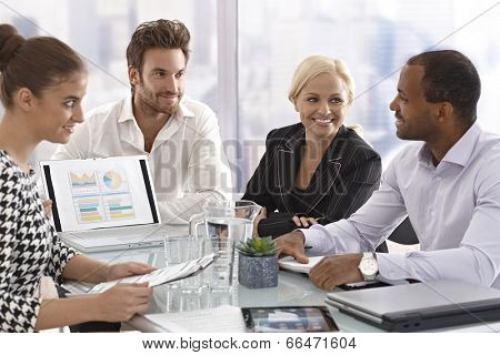 Young businesspeople sitting in meetingroom, having meeting, chatting in good mood.
