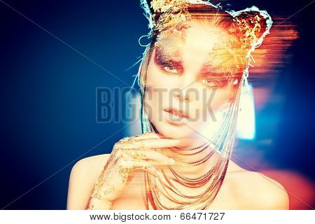 Art project: beautiful woman with golden make-up. Jewelry, make-up. Fashion. Light effects.