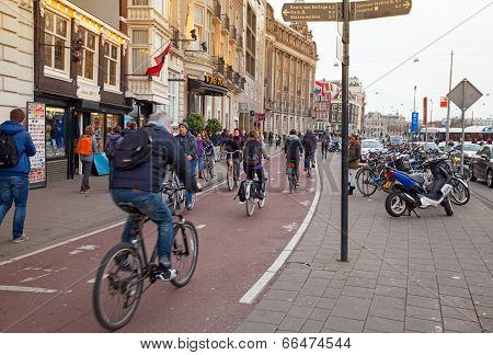Amsterdam, Netherlands - March 19, 2014: Ordinary People Walking And Ride A Bicycles On The Street