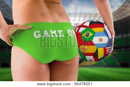 Fit girl in green bikini holding flag football against large football stadium with brasilian fans