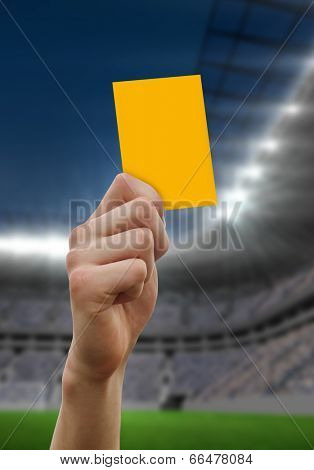 Hand holding up yellow card against football stadium