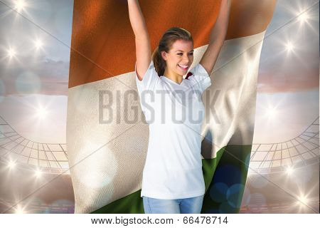 Pretty football fan in white cheering holding ivory coast flag against large football stadium under cloudy blue sky