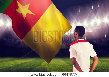 Football fan in white standing against large football stadium under night sky