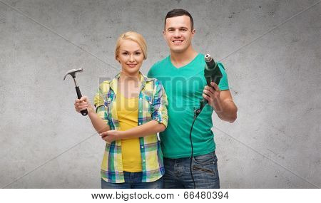 repair, construction and maintenance concept - smiling couple with hammer and drill over white background
