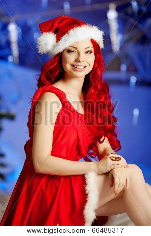 Young beauty smiling santa woman near the Christmas tree. Fashionable luxury girl celebrating New Year. Beautiful luxury trendy redhead lady.