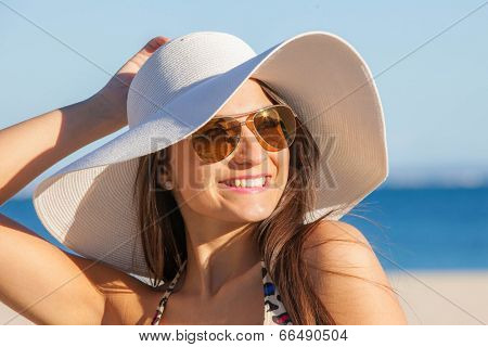 smiling woman on vacation with  sun hat and glasses.