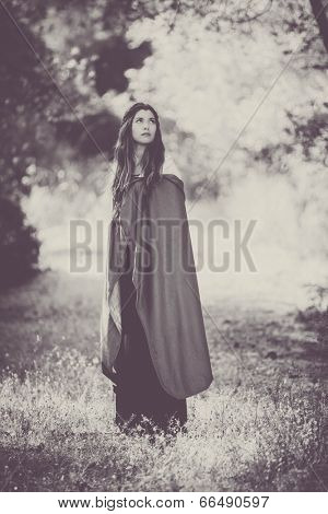 fiction woman in cloak in forest.