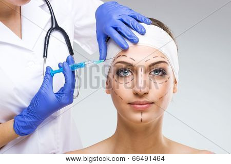 Beautiful woman with plastic surgery plastic surgeon holding a needle