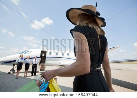 Rear view of rich woman with shopping bags walking towards private jet while pilot and stewardesses standing at airport terminal