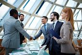 stock photo of collaboration  - Two businessmen handshaking after striking grand deal - JPG