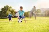 stock photo of football pitch  - Young father with his little sons playing football on football pitch - JPG