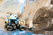 stock photo of construction machine  - Wheel loader Excavator unloading sand on construction site - JPG