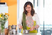 stock photo of malaysian food  - Indian woman preparing meal inside kitchen - JPG