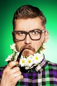 foto of peace-pipe  - Handsome young man in glasses and a beard of flowers smoking a pipe - JPG