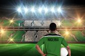 stock photo of nigeria  - Nigeria football player holding ball against stadium full of nigeria football fans - JPG